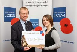 Tim Farron is pictured being presented by Legion staff member, Bethan Herbert, with a giant replica of the personalised pledge card which he has been given in recognition of his pledge.